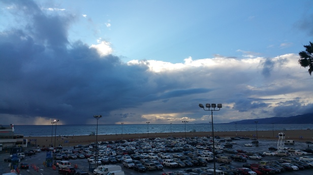 View of Santa Monica pier parking lot that also over looks beach and incoming storm