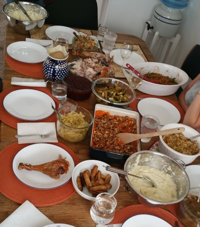 A table filled with Thanksgiving meal foods like gravy (vegan and regular), mash potatoes (vegan and regular), stuffing (vegan and regular), and vegan sweet potatoes